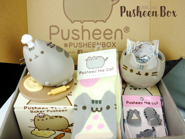 Pusheen Box Spring 2016: Baker Pusheen vinyl figure, knee high socks set, ceramic planter, key cover, and 3-piece pin set.